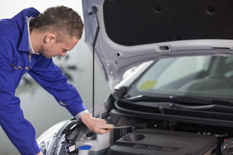 mechanic performing MOT test on car